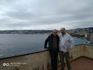 Два капитана, черный и белый, на фоне Неаполя и твердиземного моря.