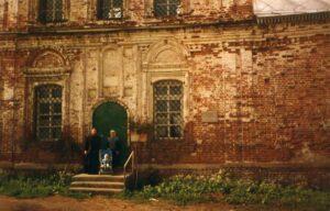 Отец Иоанн с матушкой и ребёнком на крыльце храма.