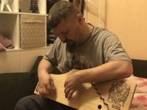 Григорий Николаевич Базлов играет на гуслях.