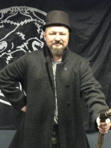 Григорий Николаевич Базлов с тросткой в традиционной русской одежде.